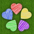 Colorful marker drawing hearts over green grass background — Stok fotoğraf #44485323