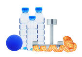 Blue bottles with water, dumbbell and ball isolated on white — Stock Photo