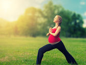 Healthy pregnant woman doing yoga in nature — Stock Photo
