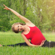 Healthy pregnant woman doing yoga in nature — Stock Photo #12543045