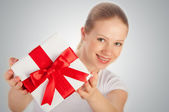 Beautiful young woman with a Christmas gift with red ribbon in t — Stock Photo