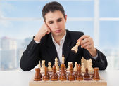 Business man playing chess, making the move — Stock Photo
