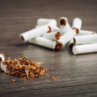 Heap of broken cigarettes and tobacco - Stock Photo