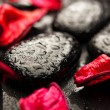 Background spa. black stones and red petals with water droplets — Stock Photo #14986271