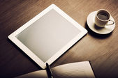 Tablet pc and a coffee and notebook with pen on the office desk — ストック写真