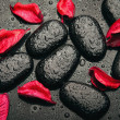 Background spa. black stones and red petals with water droplets — Stock Photo #20061561