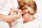 Happy family. baby and mother play, kiss, tickle, laugh in bed — Stock Photo