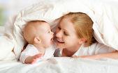 幸福的家庭。母亲和婴儿玩下毯子 — 图库照片