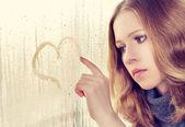 Sad girl draws a heart on the window in the rain — Stock Photo