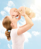Happy family. Mother kissing baby in the sky — Stock Photo