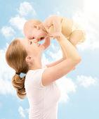 Gelukkige familie. moeder zoenen baby in de hemel — Stockfoto