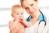 Pediatrician woman doctor holding baby — Stock Photo