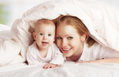 Happy family. Mother and baby playing under blanket — Stock Photo