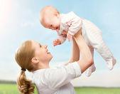 Glückliche familie. mutter wirft kind in den himmel — Stockfoto