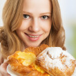Happy young woman offers treats cakes, scones, muffins, biscuits — Stock Photo