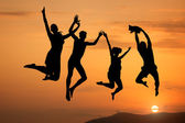 Silhouette of happy jumping at sunset — Stock Photo