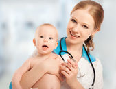 Pediatrician woman doctor holding patient baby — Stock Photo