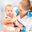 Baby and doctor pediatrician. doctor listens to heart with s — Stock Photo #24042859