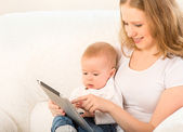 Mother and baby with tablet computer on the couch at home — Stock Photo