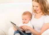 Madre e bambino con computer tablet sul divano a casa — Foto Stock