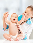 Funny baby and doctor pediatrician. doctor listens to the heart — Stock Photo