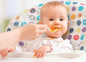 Mom feeds funny baby from spoon — Stock Photo