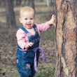 Happy baby girl  stands on legs near a tree in the park outdoors — Stock Photo