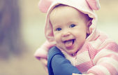 Happy smiling baby girl in pink hood with ears — Stock Photo