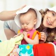 Mom and baby girl with suitcase and clothes ready for traveling — Stock Photo #25161623