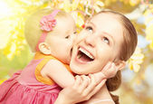 Happy cheerful family. Mother and baby kissing in nature outdoor — Stock Photo