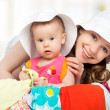 Mom and baby girl with suitcase and clothes ready for traveling — Stock Photo