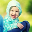 Happy baby smiling in a blue hood in the stroller for a walk in — Stock Photo