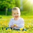 Baby girl on a green meadow with yellow flowers dandelions on th — Photo