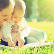 Happy family. Mom and baby in a meadow in the summer in the park — Stock Photo #26157961