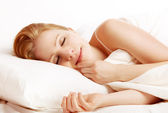 Beautiful woman sleeping and smiles in his sleep in bed — Stock Photo