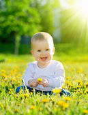 Baby girl on a green meadow with yellow flowers dandelions on th — Foto Stock