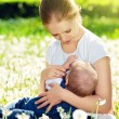 Mother feeding her baby in nature green meadow with white flower — Stock Photo