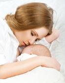 喂养她的孩子在床上的母亲。睡在一起 — 图库照片