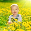 Happy baby girl on meadow with yellow flowers on the nature — Stock Photo