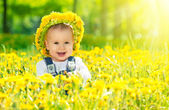 Happy baby girl in a wreath on meadow with yellow flowers on t — Stock Photo