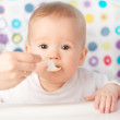 Mother feeds funny baby from spoon — Stock Photo