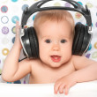 Happy baby with headphones listening to music — Stock Photo