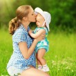 Happy family on walk. mother kissing baby — Stock Photo #27354705