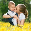 Stock Photo: Happy family on a walk. mother kissing baby