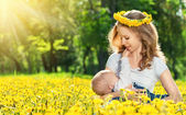 Mother feeding her baby in nature green meadow with yellow flow — Stock Photo