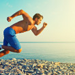 Man athlete running by the sea at sunset outdoors — Stock Photo #29691463