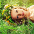 Beautiful woman in wreath of flowers lies in the green grass out — Stock Photo #29691473
