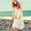 Happy family, mother and baby daughter in white dresses on the b — Stock Photo #30186545