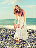 Héhé, mère et bébée fille en robes blanches sur le b — Photo