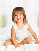 Little happy smiling cheerful girl in a bed — Stock Photo
